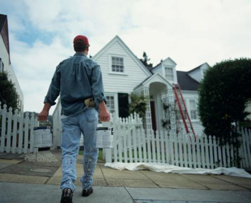 Man carrying paint tins walking towards house